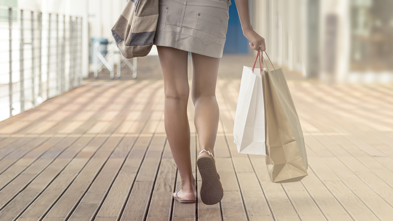 A rear shot of a woman walking on a boardwalk carrying a purse and shopping bags.